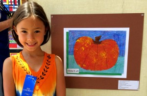 Young artist Olivia Ganes with her painting, The Pumpkin